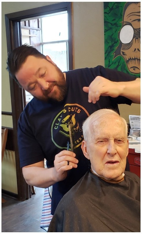 Clay, the owner of Clay's Cuts, giving a haircut to an older man. Looking sharp fellas!