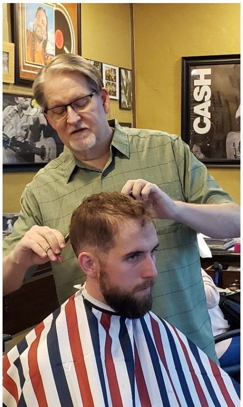 Phil giving a haircut to a young man. Looking sharp!