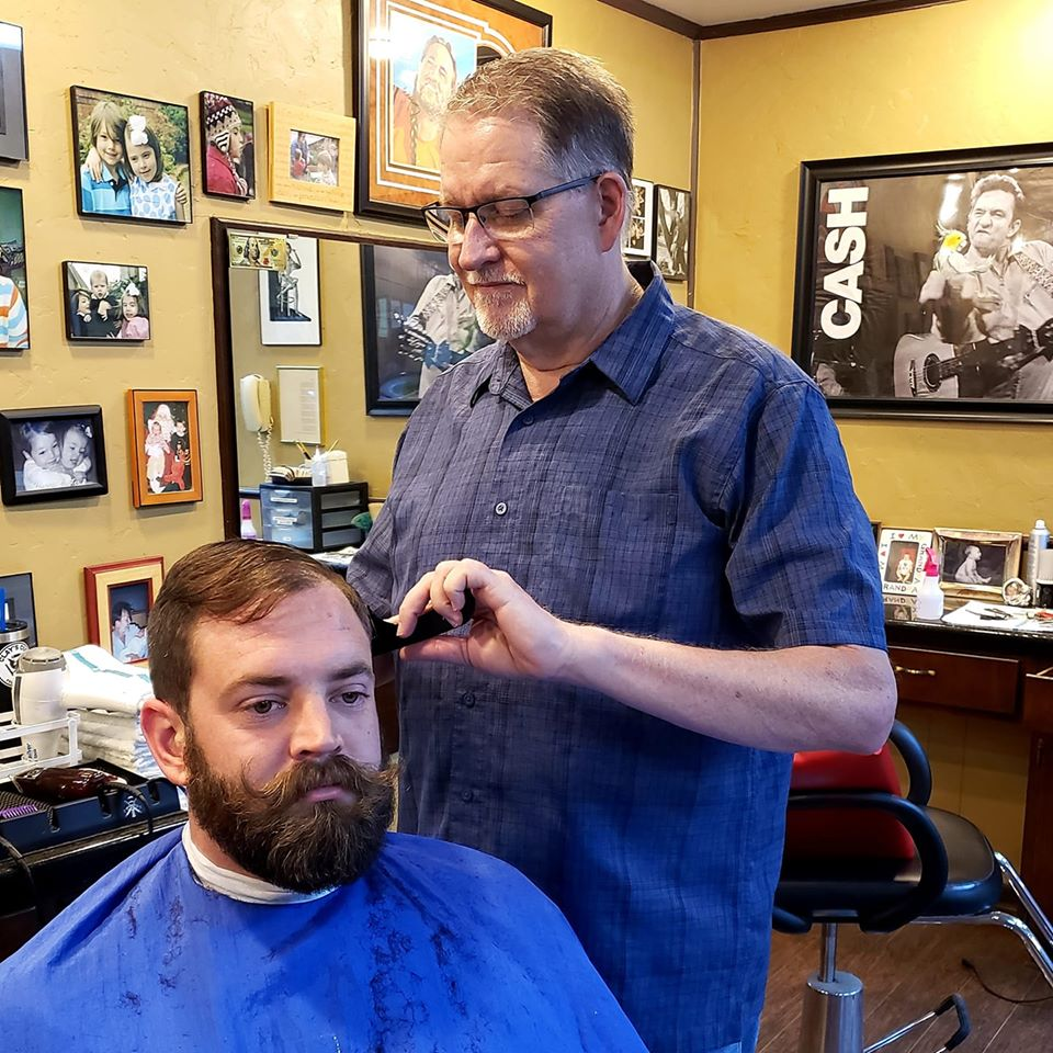 Phil working on a haircut AND beard carving on a dark-haired man. Perfection!